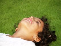 Smiling girl looking up. Closeup of a happy, smiling, young asian girl with dark curly hair, laying in the grass and looking up Royalty Free Stock Photo