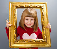 Smiling girl looking through a vintage picture frame Royalty Free Stock Photo