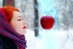 Smiling girl looks at hanging in air big red apple Stock Photo