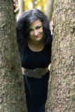 Smiling girl looks out from under trees Royalty Free Stock Images
