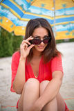 Smiling girl looks over glasses under umbrella in the sand Stock Image