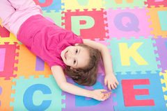 Smiling girl lying on alphabet tiles Royalty Free Stock Photos
