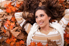 Smiling girl lying on autumn leaves royalty free stock photos