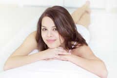 Smiling girl lying in bed Stock Photos