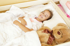 Smiling girl lying on bed with big teddy bear Royalty Free Stock Images