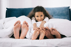 Smiling girl lying in bed with father and mother. Adorable smiling girl lying in bed with father and mother Royalty Free Stock Photos