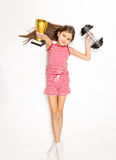 Smiling girl lying on floor with dumbbell and golden trophy cup Stock Photos