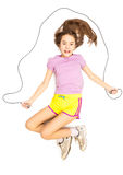 Smiling girl lying on floor and pretending to skip with rope Royalty Free Stock Image