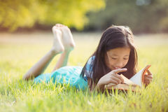 Smiling girl lying on grass and reading book in park Royalty Free Stock Photos