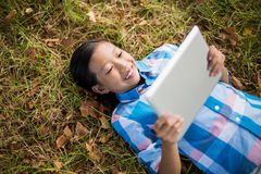 Smiling girl lying on grass and using digital tablet Stock Images
