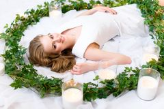 Smiling girl lying in a green wreath looking straightly into the camera, happiness and youth in her glance. Beauty and health royalty free stock images