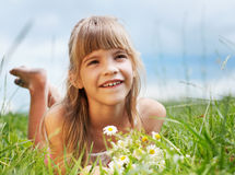 The smiling girl is lying in the meadow. The smiling girl is lying in the green meadow Stock Photo
