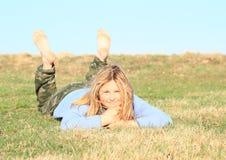 Smiling girl lying on meadow stock photos