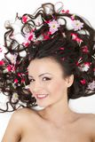 Smiling Girl lying with red flowers in her hair Stock Photo