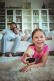 Smiling girl lying on rug and changing channels Royalty Free Stock Image