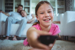 Smiling girl lying on rug and changing channels. At home stock image