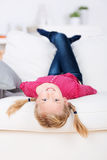 Smiling Girl Lying Upside Down On Sofa Stock Image