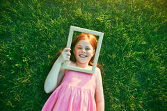 Smiling girl lying with wooden frame Royalty Free Stock Image
