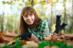 Smiling girl lying on yellow leaves outdoors Royalty Free Stock Photo