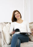 Smiling girl with magazine on sofa Royalty Free Stock Images
