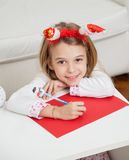 Smiling Girl Making Christmas Greeting Card Stock Image