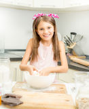 Smiling girl making dough for pie in white bowl Stock Photography