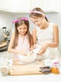 Smiling girl making dough in white bowl on kitchen Royalty Free Stock Photo