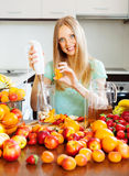 Smiling girl making fruits beverages Royalty Free Stock Images