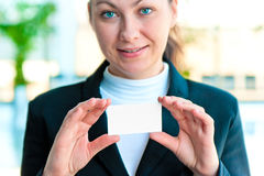 The smiling girl the manager holds the empty business card before herself Stock Images