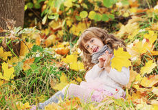 Smiling girl with  maple leaves Stock Images