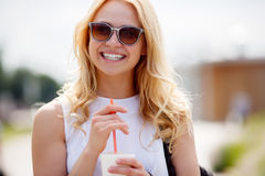Smiling girl with milk cocktail outdoors. Blonde smiling girl with milk cocktail outdoors Royalty Free Stock Photo