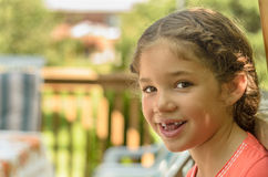 Smiling girl missing front teeth. Beautiful girl sitting on the back porch smiling and showing her missing front teeth Royalty Free Stock Images