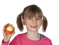 Smiling girl with missing milk teeth and bitten apple Stock Images