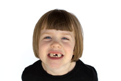 A smiling girl missing teeth. A young girl with a big cheesy smile, missing teeth Royalty Free Stock Photos