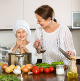 Smiling girl and mom at kitchen Royalty Free Stock Photo