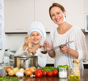 Smiling girl and mom at kitchen Royalty Free Stock Photography