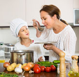 Smiling girl and mom at kitchen Stock Photos