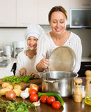 Smiling girl and mom at kitchen Royalty Free Stock Photos