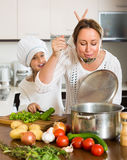 Smiling girl and mom at kitchen Stock Photography