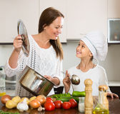 Smiling girl and mom at kitchen Royalty Free Stock Image