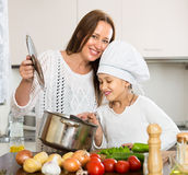 Smiling girl and mom at kitchen Stock Images