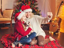 Smiling girl with mom near christmas tree at home Stock Image