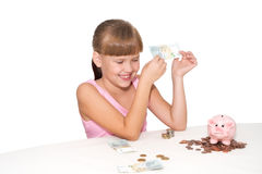 Smiling girl with money in hands  isolated. Smiling little  girl with money in hands and piggy bank  on  table isolated Stock Images