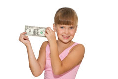 Smiling girl with money in hands isolated. Smiling little girl with money in hands and piggy bank  on  table isolated Stock Photography