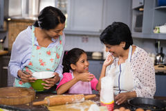 Smiling girl with mother and grandmother preparing food in kitchen Royalty Free Stock Photo