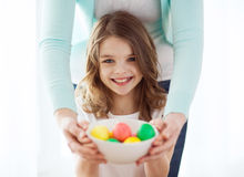 Smiling girl and mother holding colored eggs Royalty Free Stock Images
