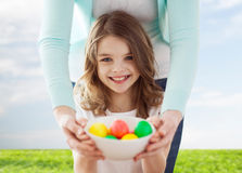 Smiling girl and mother holding colored eggs Stock Image