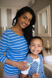 Smiling girl with mother holding toothbrushes in bathroom stock photos