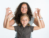 Smiling girl with mother showing ok sign. On a white background Royalty Free Stock Image