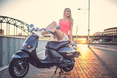 Smiling girl on moto scooter. Smiling sexy blond girl in summer clothing posing on moto scooter over white sky Stock Photography